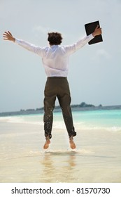 Happy young white-collar worker jumping on the shore of the sea view from behind