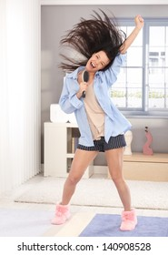 Happy young woman acting as pop star, using hairbrush as microphone, wearing pyjamas, long hair flying in the air.