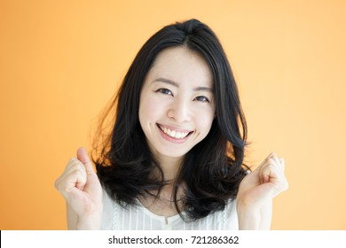 Happy young woman against orange background