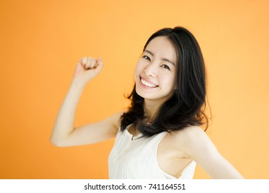 Happy young woman against orange background.