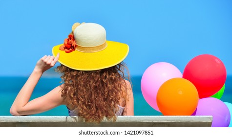 Happy young woman with an air colorful balloons is enjoying a summer day on a beach blue sky background.
