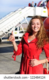 happy young woman in airport near the airplane