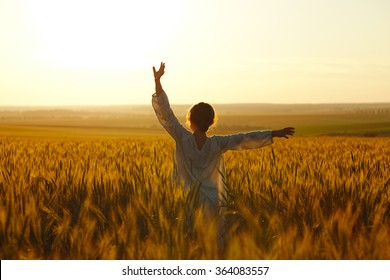Happy young woman among rye field in the evening