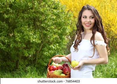 Happy young woman with apples at the basket. Spring Garden