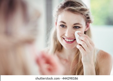 Happy young woman applying blush while looking in mirror