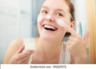 Happy young woman applying cleansing moisturizing skin cream on face. Girl taking care of dry complexion layering moisturizer. Skincare.
