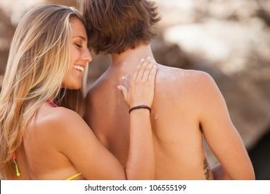 Happy young woman applying cream on boyfriend's back