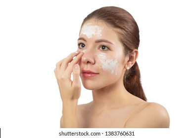 happy young woman applying cream on her face skin, isolated on white background, smiling
