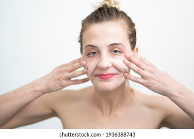 Happy Young Woman Applying Cream on Her Face, Studio Shot on White Background