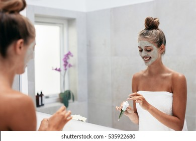 Happy young woman applying face mask in bathroom and smiling. Beautiful female in front of mirror doing beauty treatment.