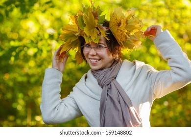 Happy young woman with autumn maple leaves garland in park