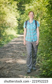 A happy young woman with a backpack hikes on a trail among nature.