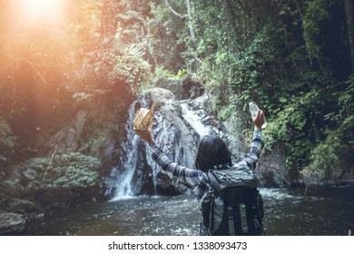 Happy of young woman with backpack standing in front of waterfall. Travel concept.