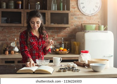 Happy young woman baking pie in loft kitchen at home, using book with recipe, copy space