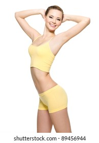 Happy young woman with beautiful slim body in yellow sport clothes -  isolated on white background