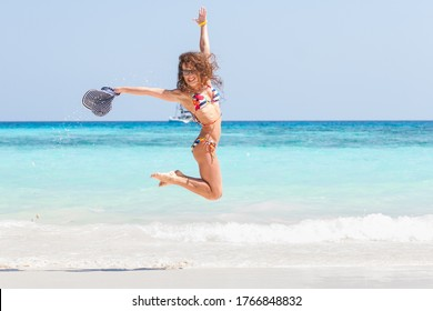 Happy young woman in bikini jumping on the beach on blue ocean background