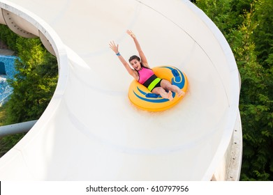Happy young woman in bikini on a rubber inflatable float on a water slide, playing and having a good time at water fun park pool, on a summer hot day