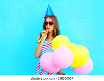 Happy young woman in a birthday cap blowing a whistle holds an air colorful balloons on a blue background
