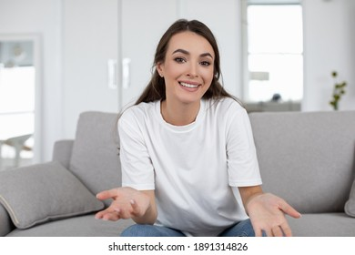Happy young woman blogger influencer sit at home speaking looking at camera talking make video chat, webcam view.