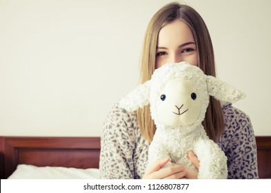 Happy young woman with blonde hair sitting on the bed in her bedroom in an embrace with a stuffed animal toy. Favorite white sheep in the hands of teen girl in cute warm pajamas.