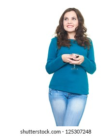 Happy young woman in a blue shirt holding a glass of wine and looking at the upper-right corner. Isolated on white background