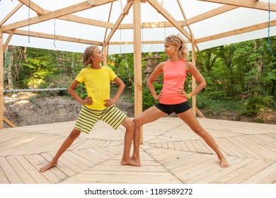 happy young woman and boy doing yoga outdoors. Mother exercising with her son.