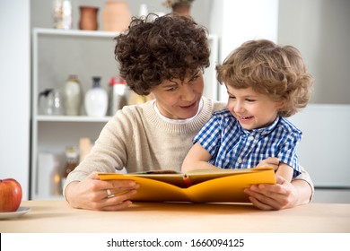 Happy young woman and young boy reading a book