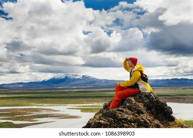 Happy young woman in bright clothes traveling Iceland, enjouing nature