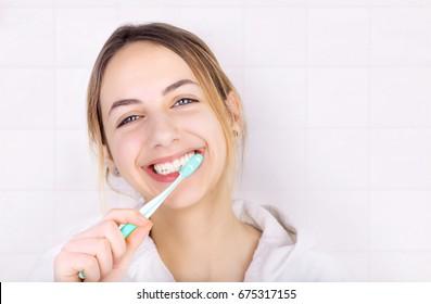Happy young woman brushing teeth .