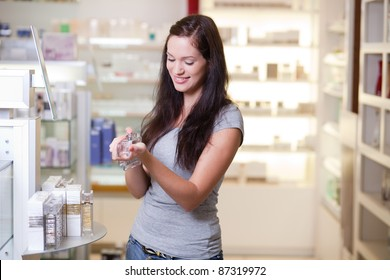 Happy young woman buying a perfume