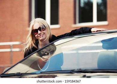 Happy young woman at the car