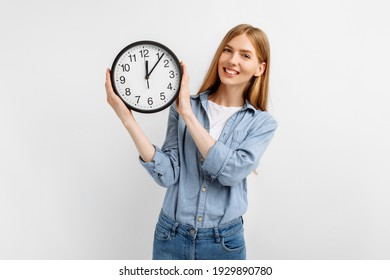 Happy young woman in casual clothes holding clock over isolated white background