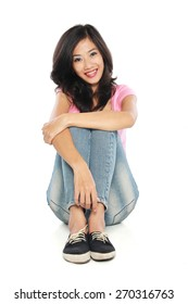 Happy young woman in casual wear smiling sitting on the floor. Isolated on white background