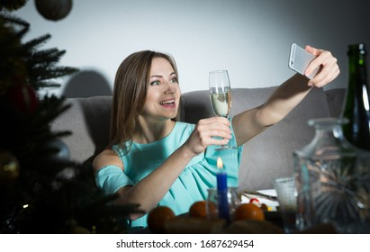 Happy young woman celebrating Christmas at home alone, taking selfie with glass of wine