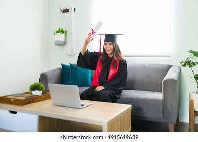 Happy young woman celebrating during a video call in a virtual ceremony. College graduate in a graduation gown raising in the air her university diploma while sitting in the living room