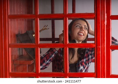 Happy young woman chatting on a public phone in a red telephone booth smiling with delight as she listens to the conversation
