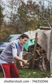 Happy young woman chopping wood in her backyard.