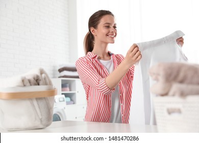 Happy young woman with clean shirt indoors. Laundry day