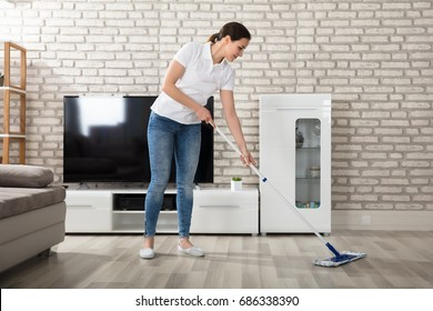 Happy Young Woman Cleaning The Hardwood Floor With Mop In Living Room
