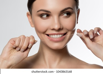 Happy young woman is cleaning her teeth by dental floss. She is standing and smiling. Isolated