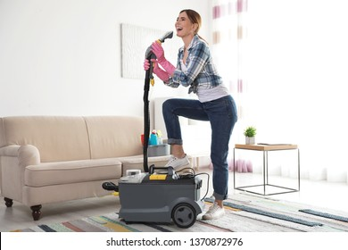 Happy young woman cleaning home with vacuum cleaner and having fun indoors