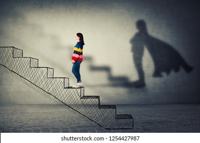 Happy young woman climbing a imaginative stairway with aspiration of becoming superhero. Dream of success, inner power and confidence symbol.