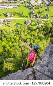 """Happy young woman climbing a via ferrata iron ladder on the """"Echernwand"""" route, above Hallstatt, Austria, during a climbing trip, in the Summer of 2018"""