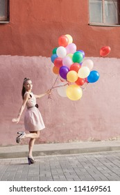 Happy young woman with colorful balloons walking on a street - outdoors