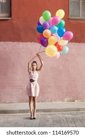 Happy young woman with colorful balloons standing on a street - outdoors
