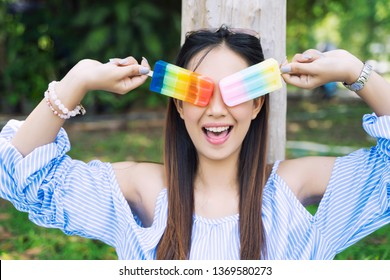 Happy young woman with colorful ice cream in hands in garden. Lifestyle and relaxing concept.