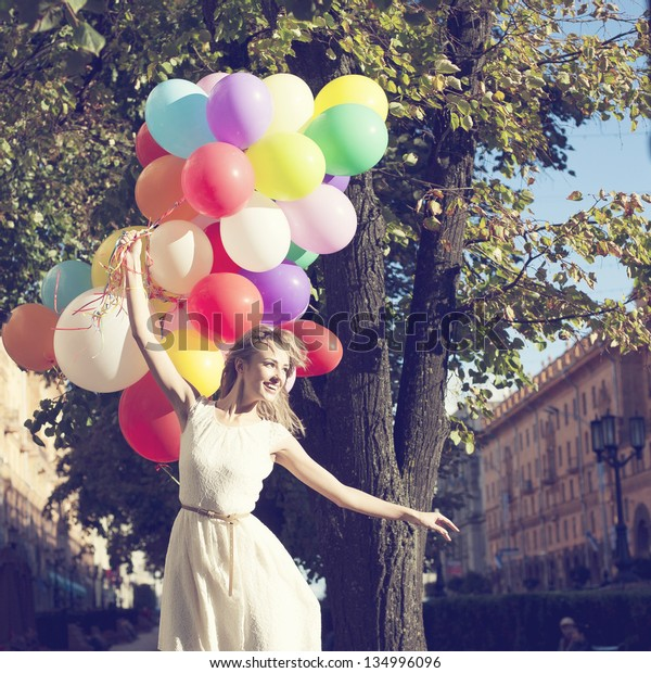 Happy young woman with colorful latex balloons, outdoor