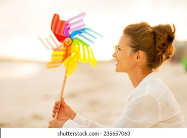 Happy young woman with colorful windmill toy sitting on beach at the evening
