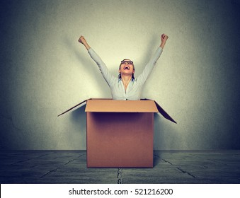 Happy young woman coming out from a small box