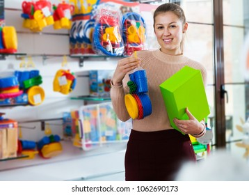 happy young woman consumer with color box among children's toys in the store
